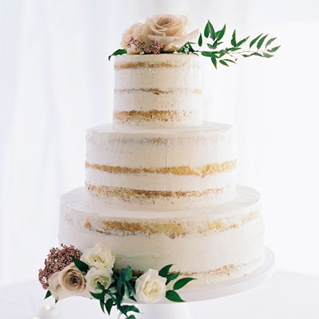 An almost-naked white wedding cake topped with blush-hued roses and rustic greenery