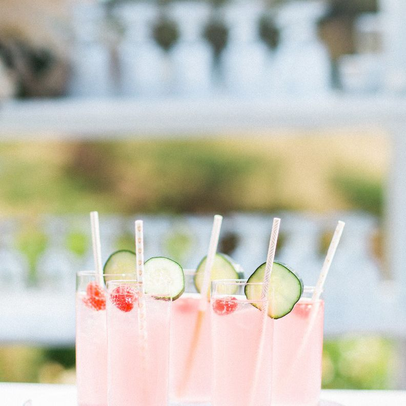 Tray of pink signature cocktails with cucumber garnish