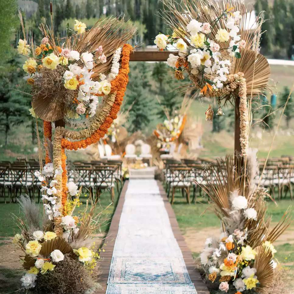 Arch decorated with pampas grass, quicksand roses, playa blanca roses, and marigolds