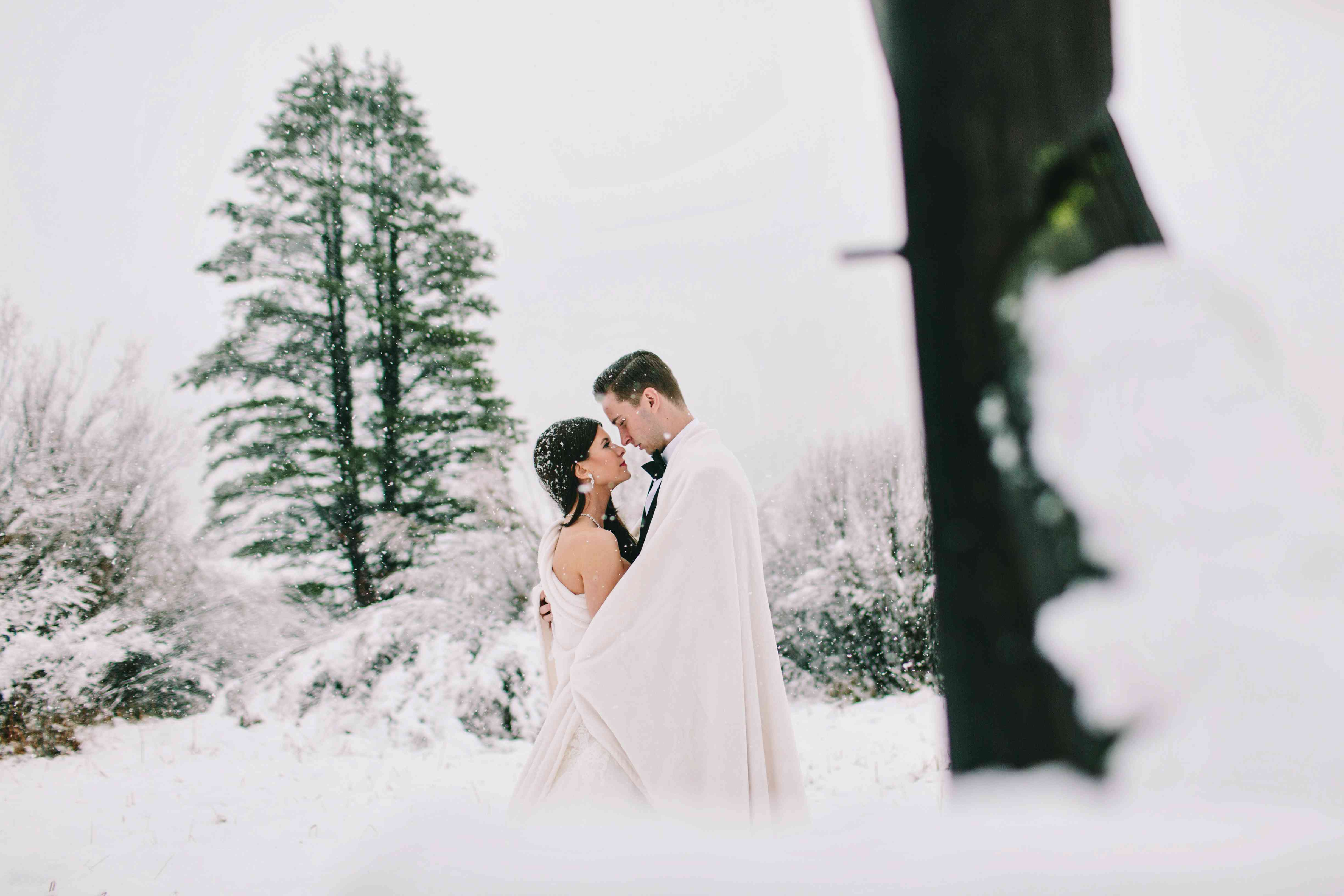 Bride and groom holding each other close in the snow outside