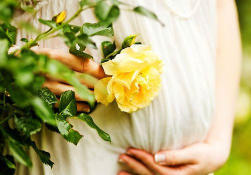Woman cradling pregnant belly beside yellow rose