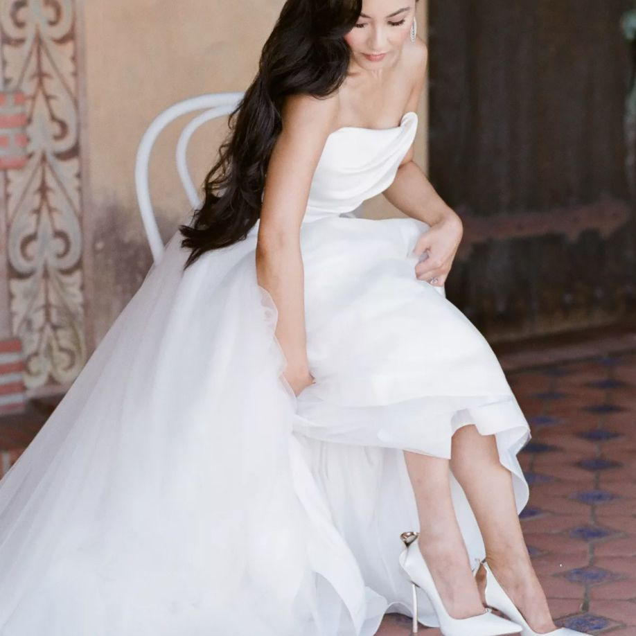 Bride lifting wedding dress to show off shoes