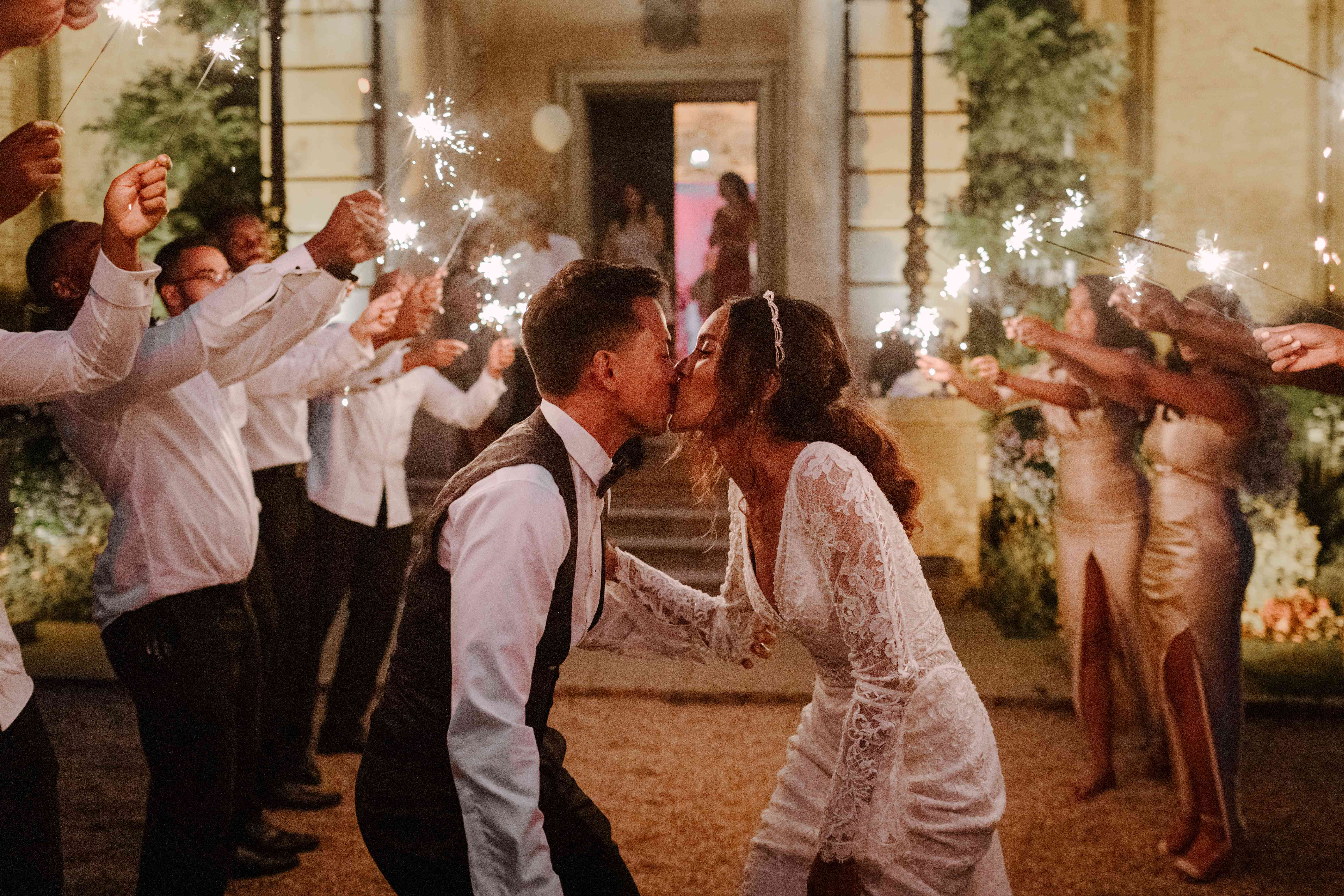 The bride and groom kiss surrounded by sparklers