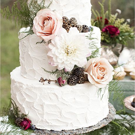A three-tiered white wedding cake by Elise Cakes with texturized frosting, lush blooms, and rustic pinecones