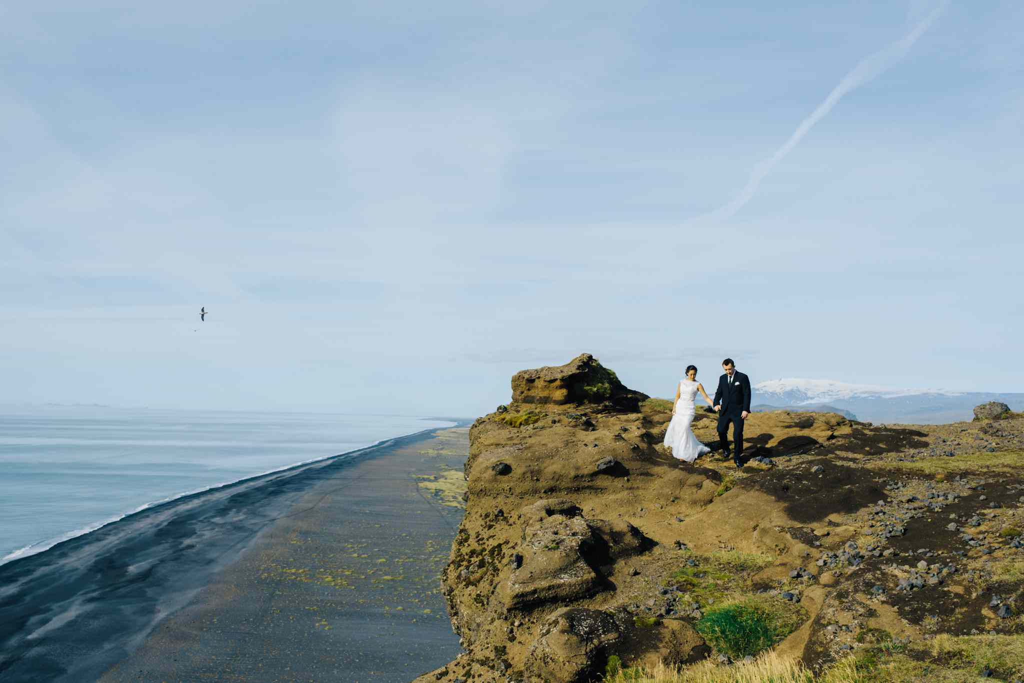 Couple holding hands on a blue sky day in Iceland