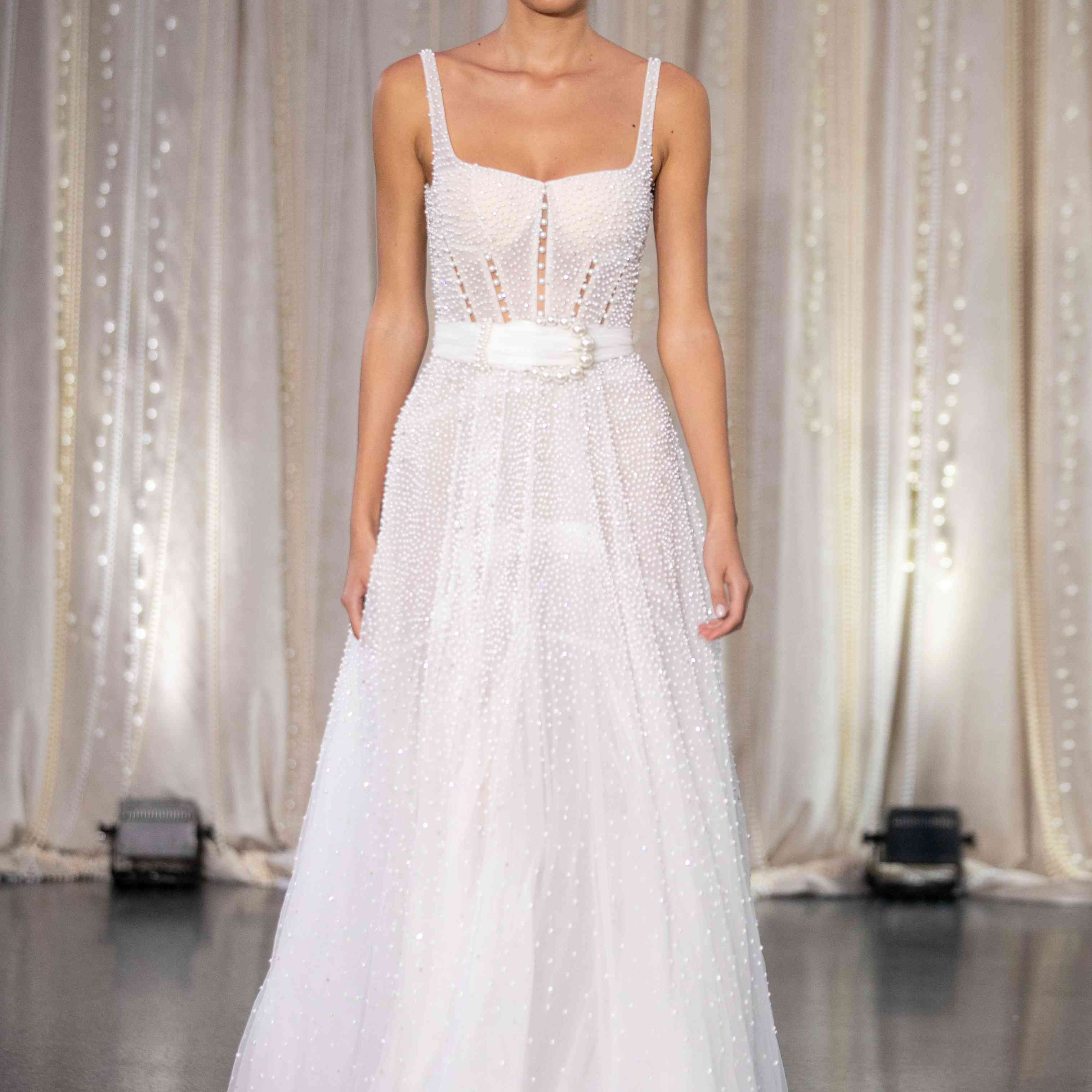 Model in sleeveless A-line wedding dress with pearls