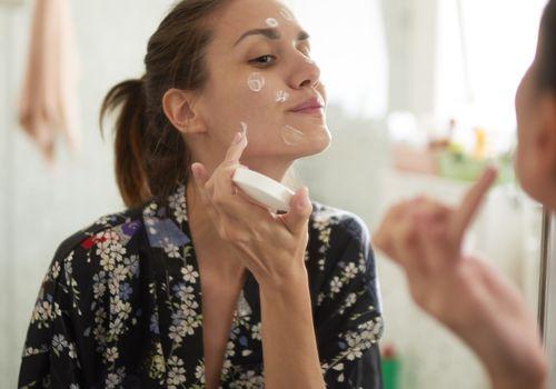 Woman applying face cream in bathroom mirror
