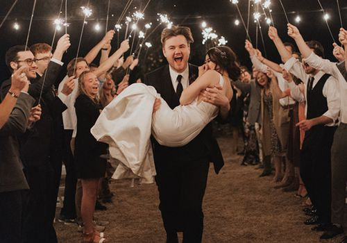 Groom carrying bride through sparklers