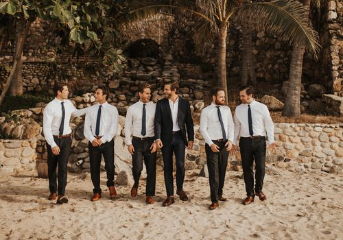 Groomsmen and groom on sandy beach in front of old stone structure and palm trees