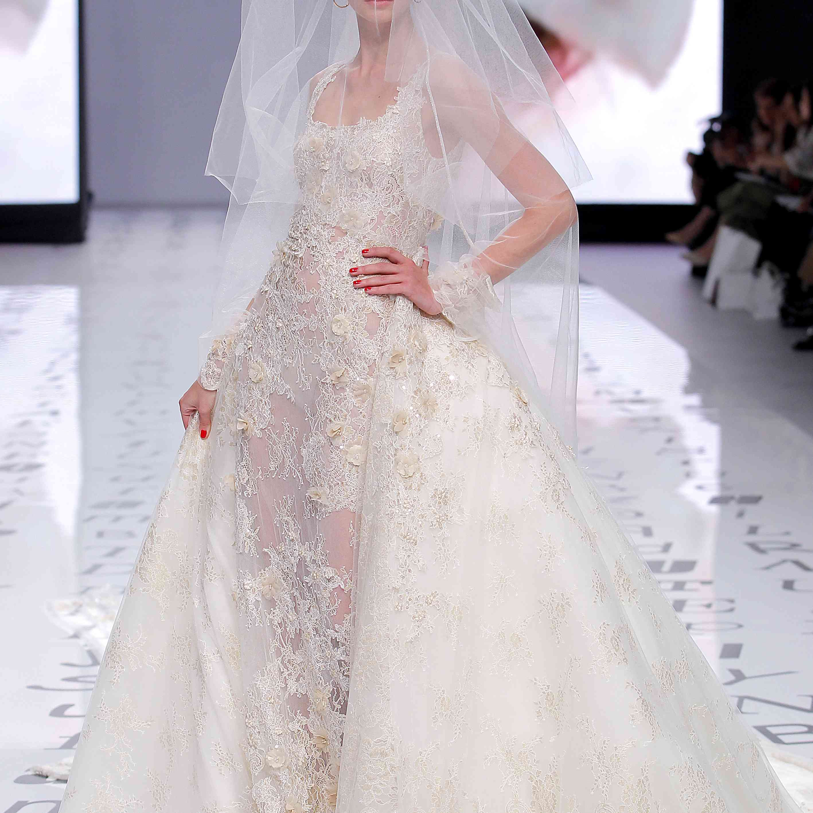 Model in a mermaid dress embroidered with sequins and 3D flowers in nude tones and a removable overskirt with layers of tulle and lace