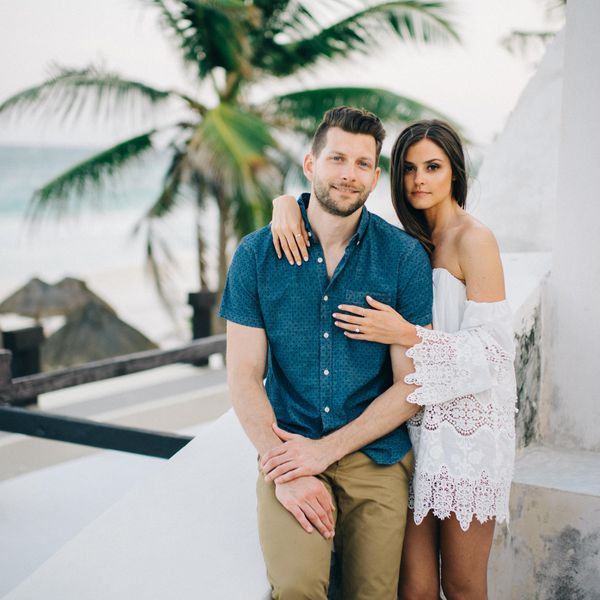 Man and woman posing with palm tree in background