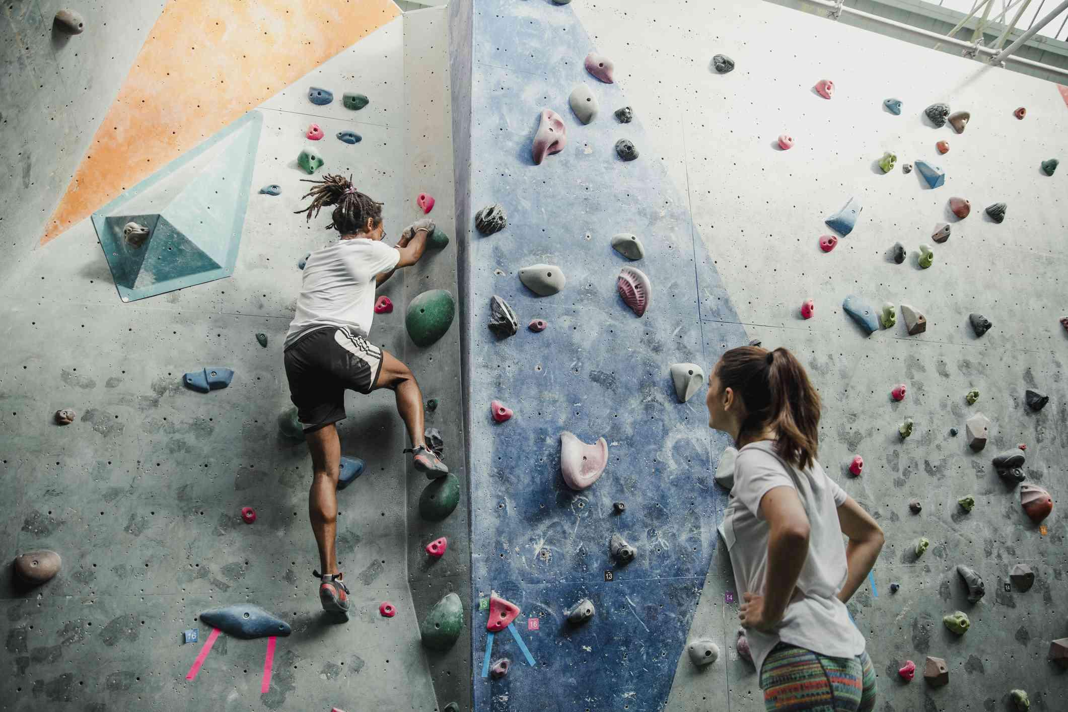 Girl watching her friend rock climb indoors