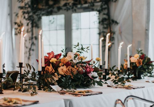 wintry table setting with white candlesticks, greenery, and roses