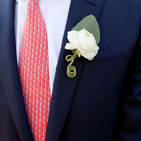 A classic white boutonniere comprised of a single overblown ranunculus created by Island Ambiance