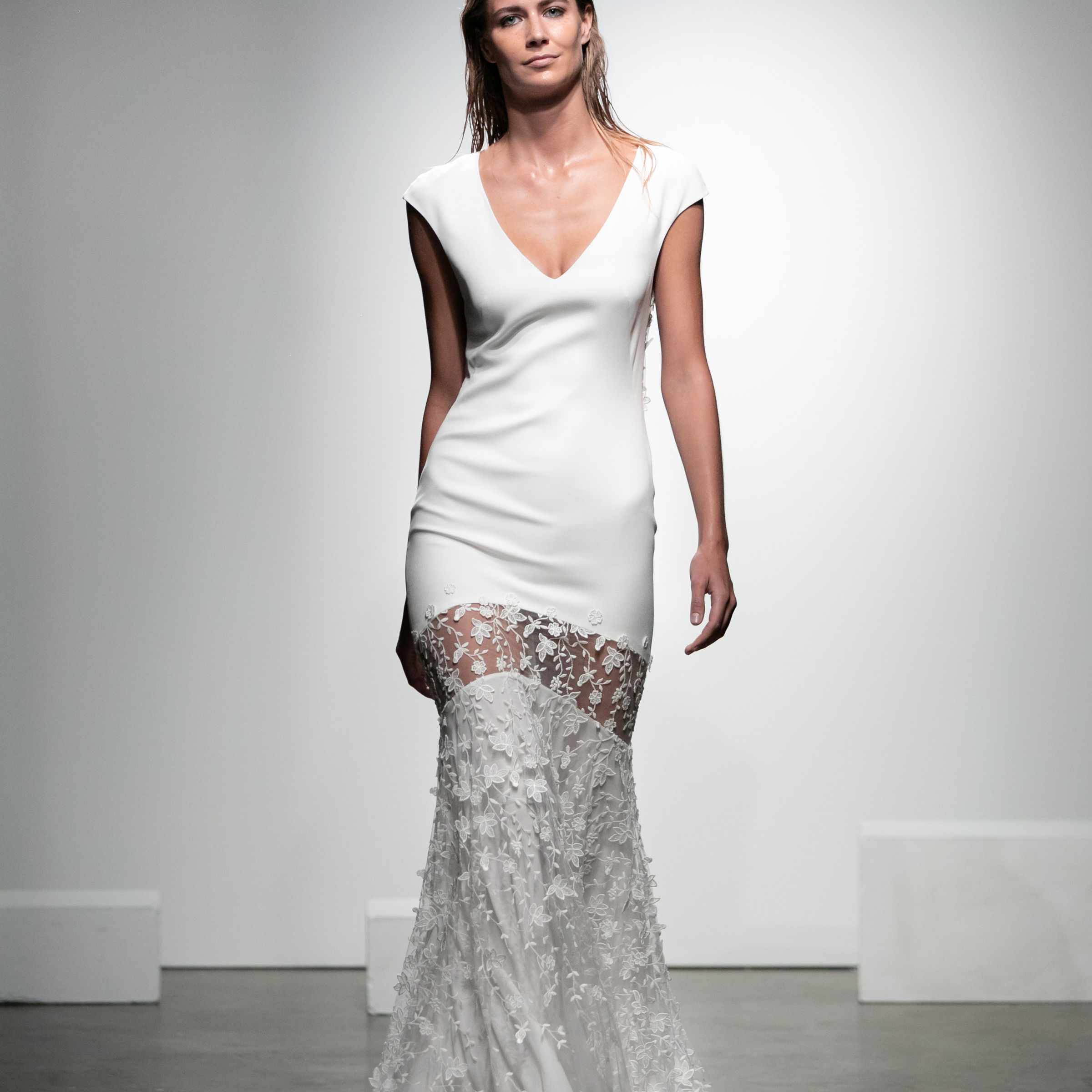 Model in V-neck crepe dress with cap sleeves and a 3D floral-embroidered tulle skirt