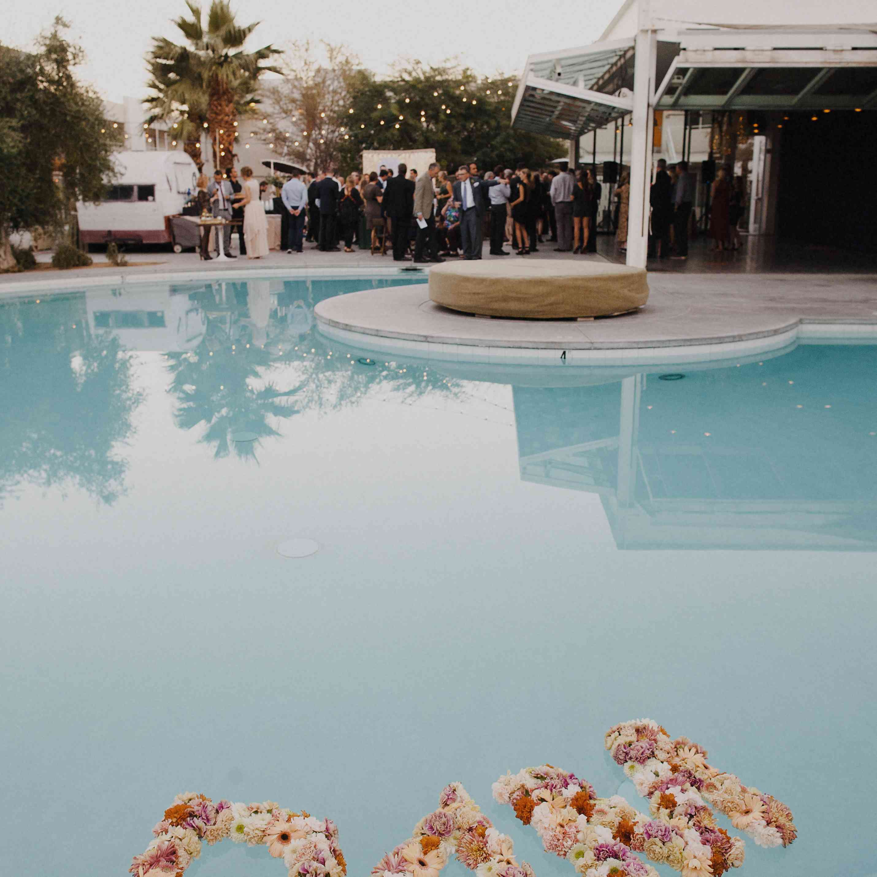 The letters D A M made of flowers floating in a pool at a wedding reception