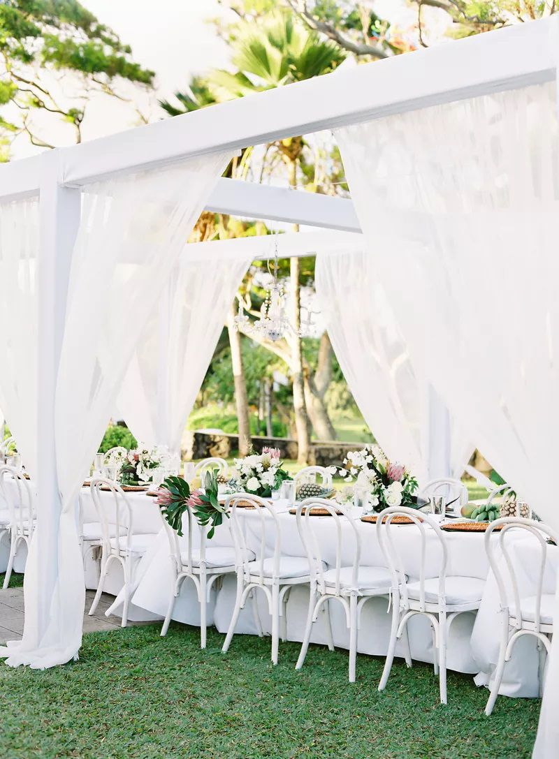 Wedding reception with white chairs and white linens