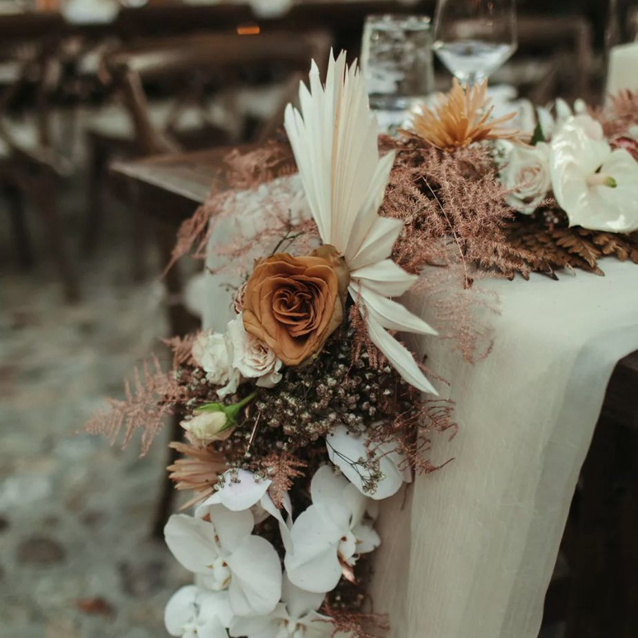 Floral table runners of orchids, dusty roses, anthurium, and dried palm leaves
