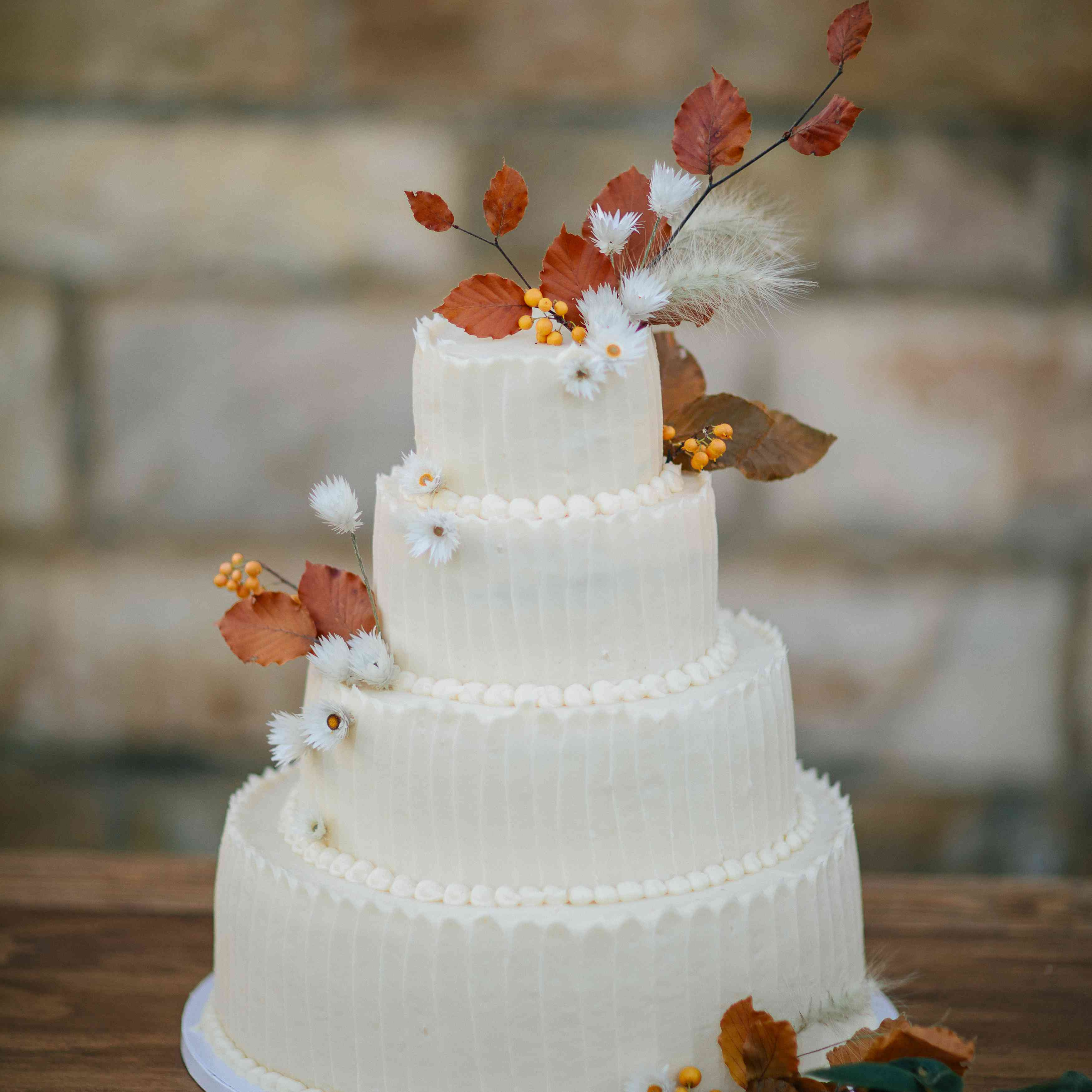Tiered fall-themed wedding cake with leaves and dried grass accents
