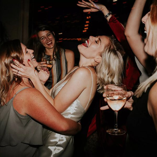 Women drinking and dancing at wedding after-party