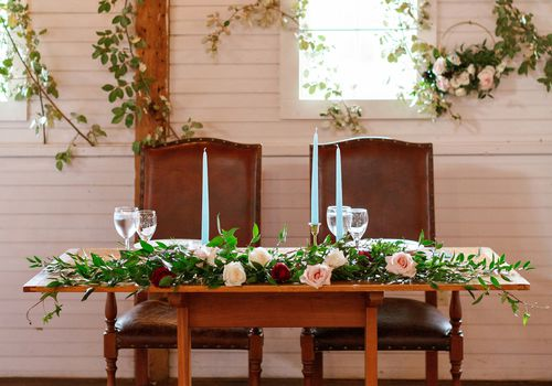 Wooden sweetheart table with blue pillar candles