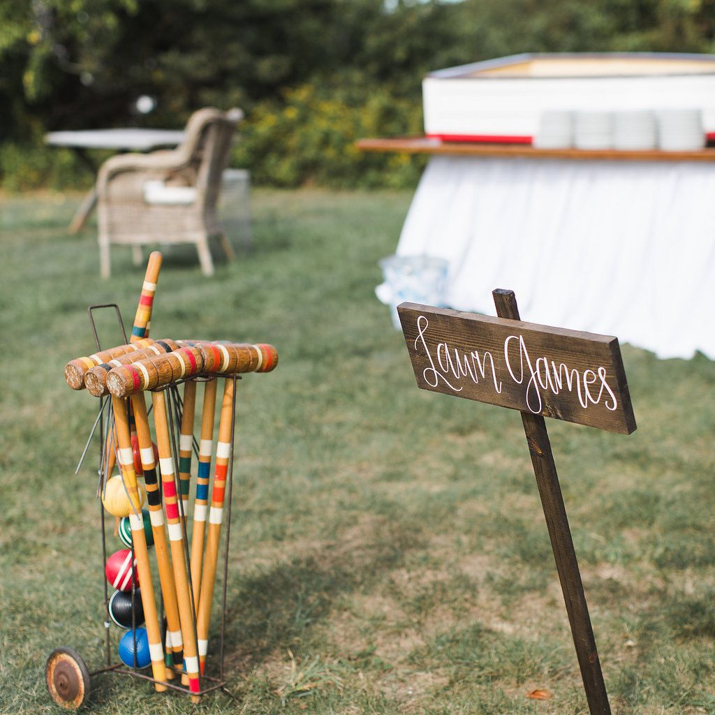Croquet mallets next to a wooden lawn games sign