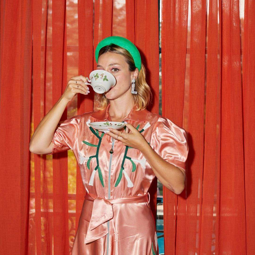 Woman sipping †ea from teacup.