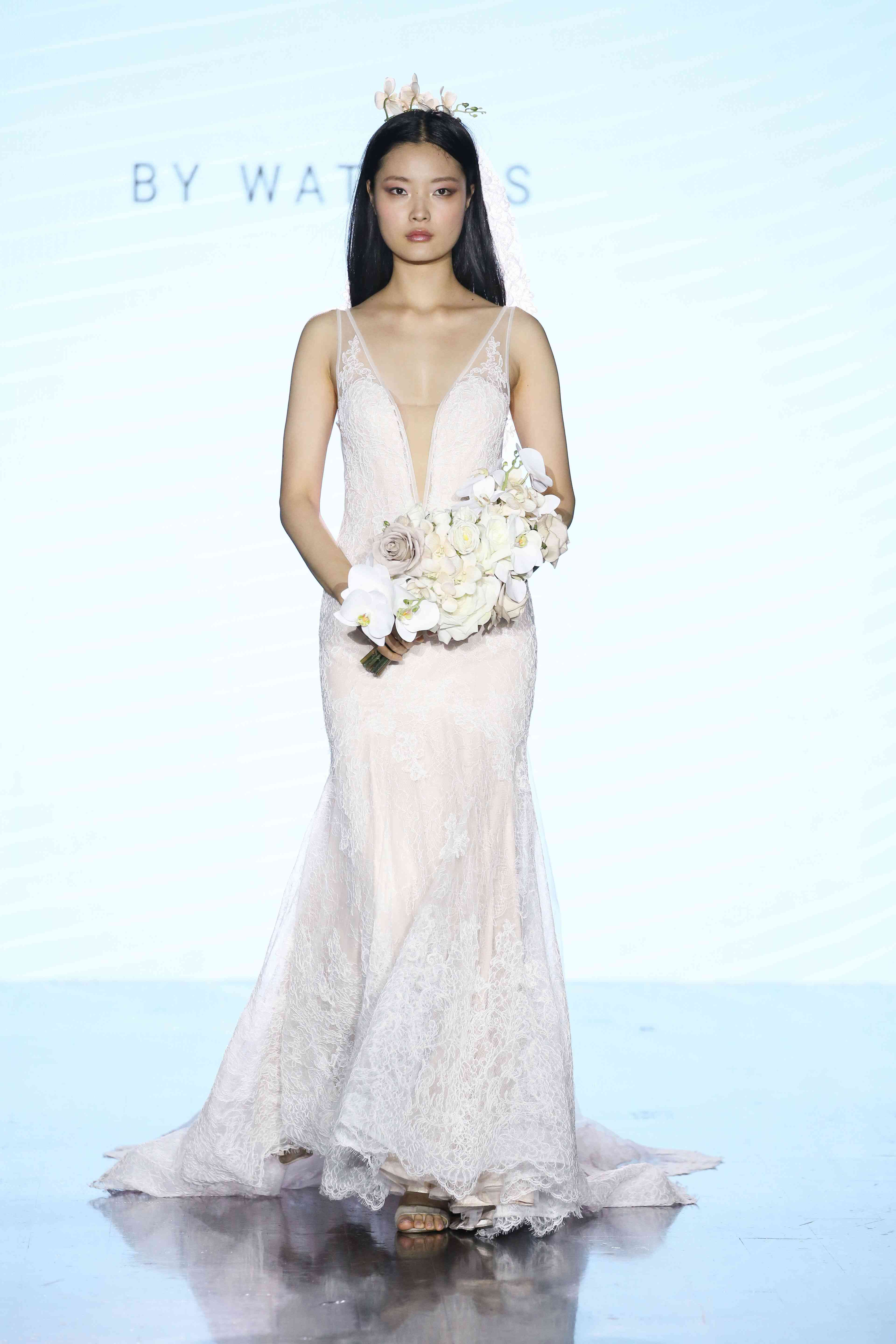 Model in fit-and-flare allover lace wedding dress with plunging illusion neckline