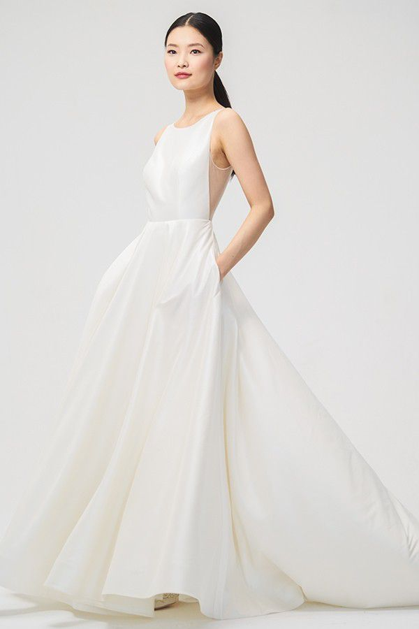 Model in high neck white wedding gown with pockets