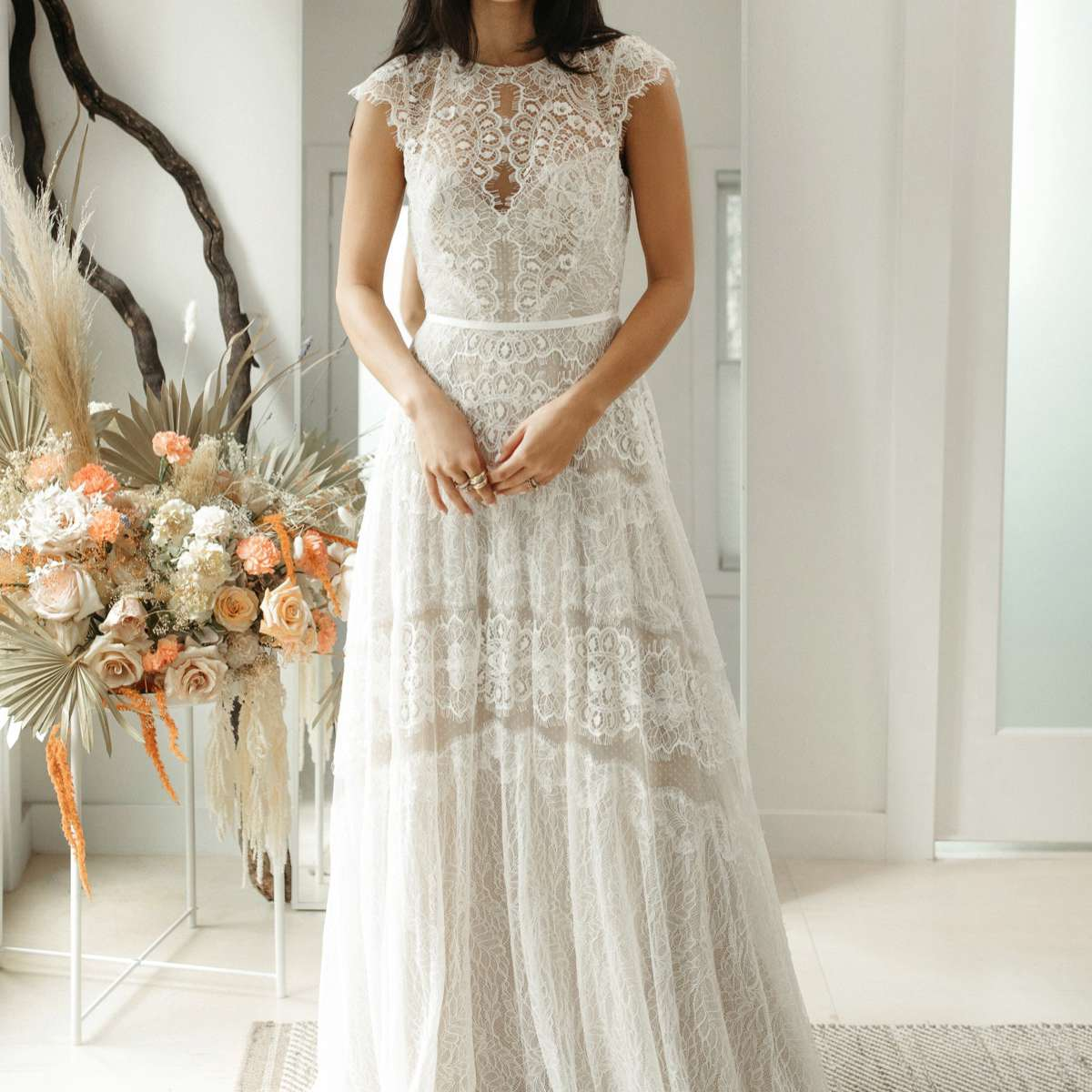 Model in jewel-neck A-line lace gown with cap sleeves