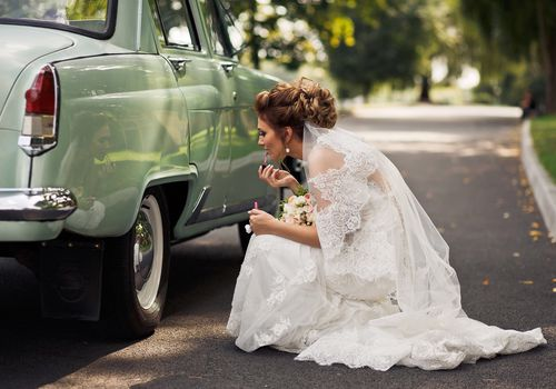 Side view of bride applying lipstick by a car