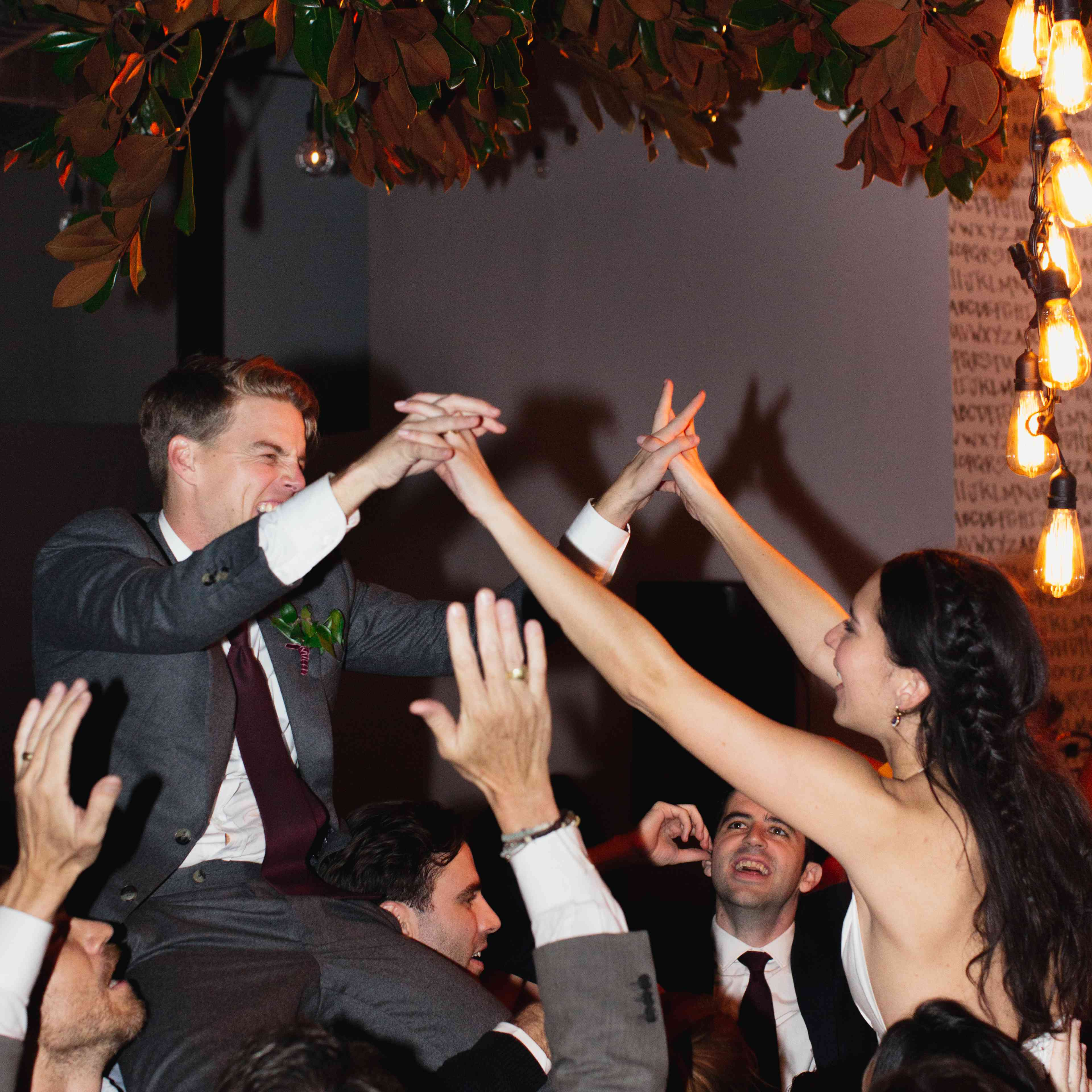 Bride and groom lifted up during dance