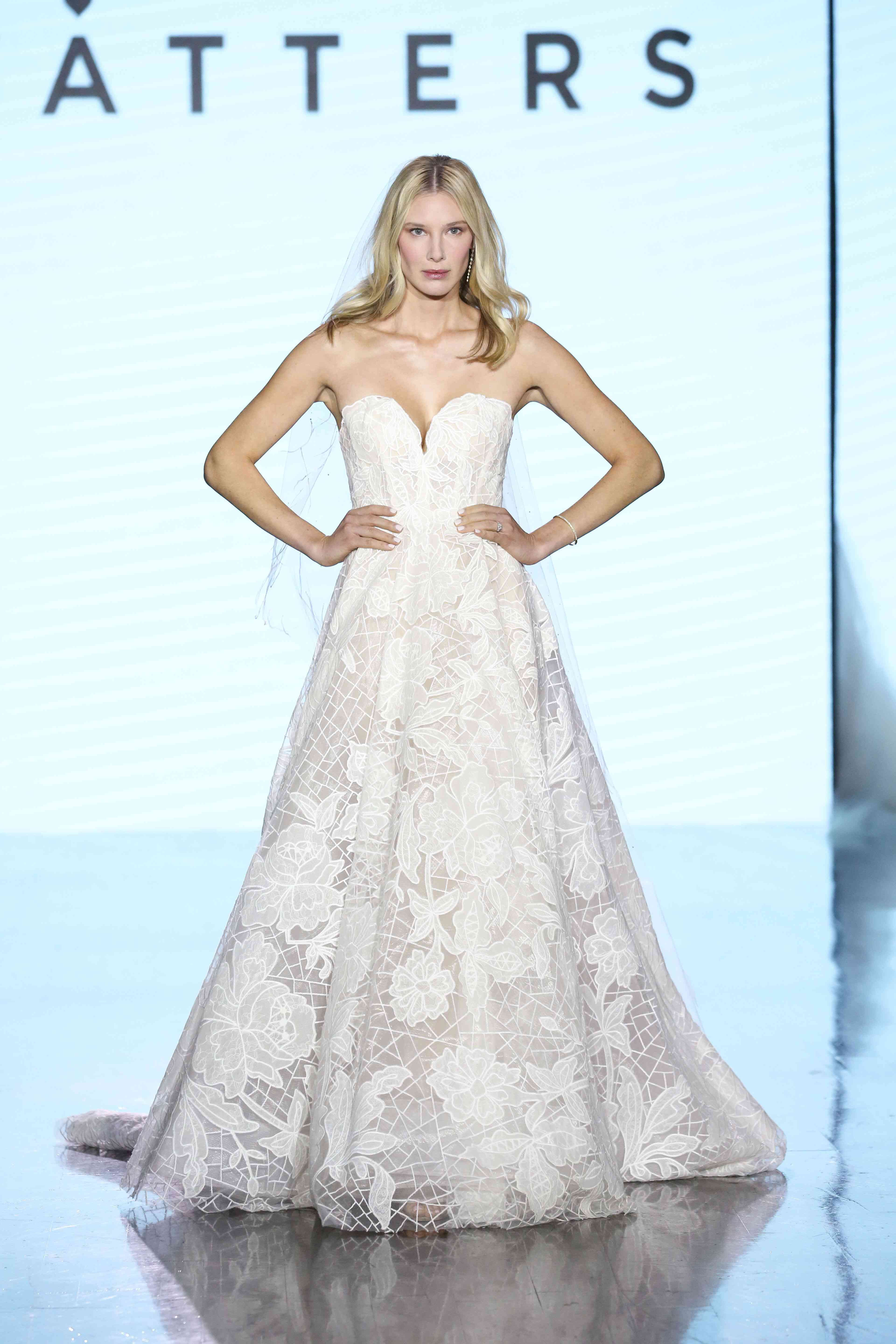 Model on runway in a strapless sweetheart floral lace A-line wedding dress