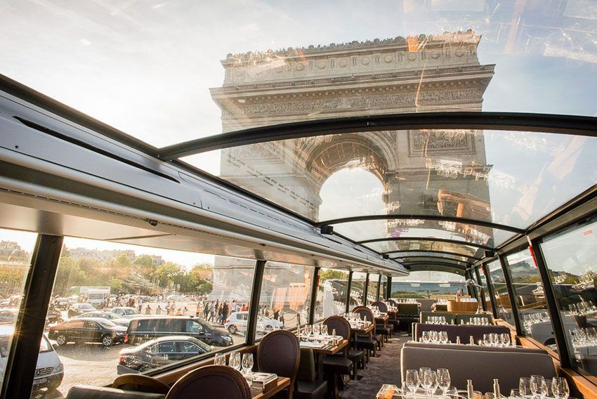 Inside of restaurant bus with all glass roof and ceiling with view of the Arc de Triomphe