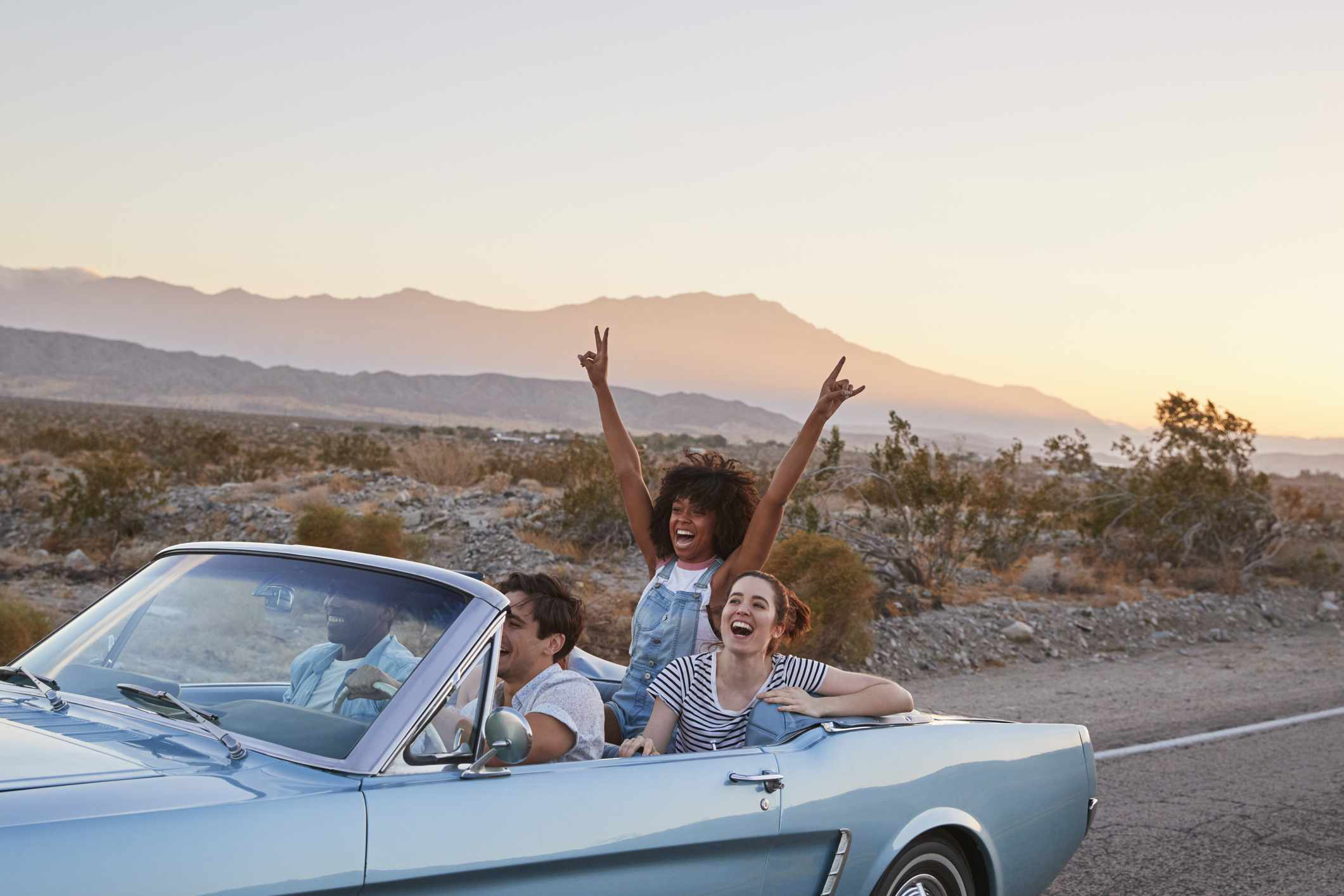 Four friends driving down a desert road in a convertible