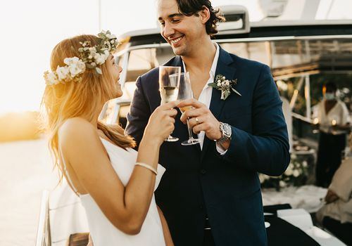 bride and groom toasting on a boat