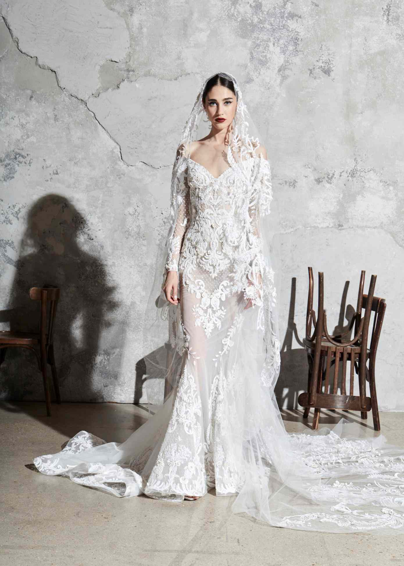 Model in off-the-shoulder long-sleeve embroidered silk organza mermaid gown with appliques and a matching veil