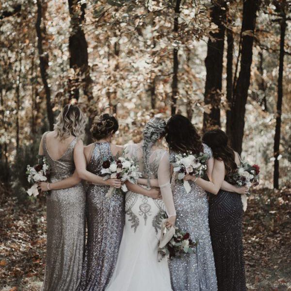 Bridesmaids wearing an array of sparkling pewter, silver, and black dresses.