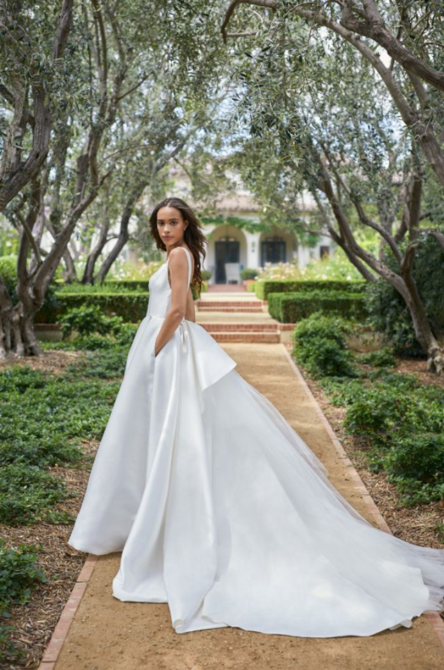 Model in white dress with bow in back and side pockets