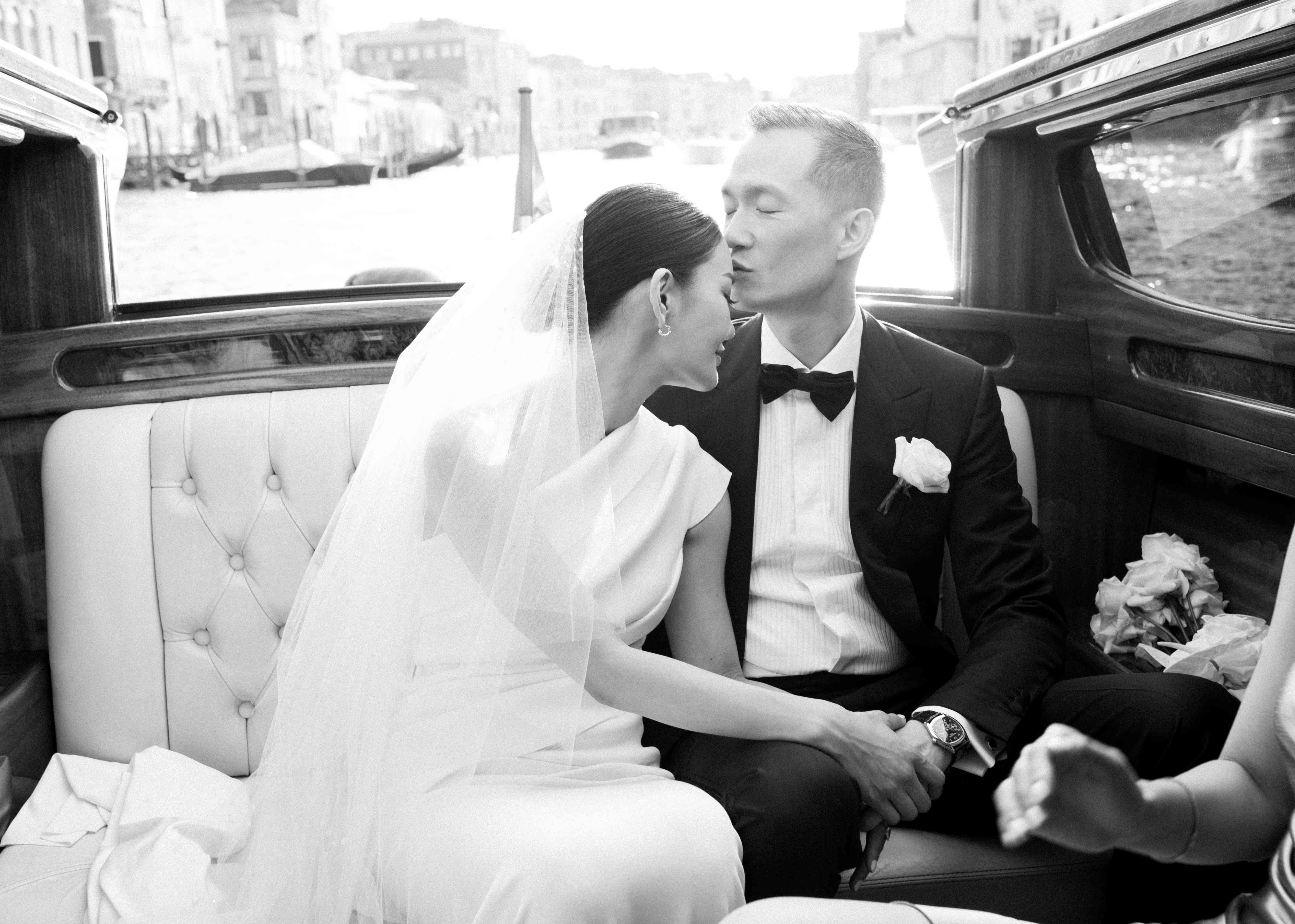 modern venice wedding, groom kissing bride gondola