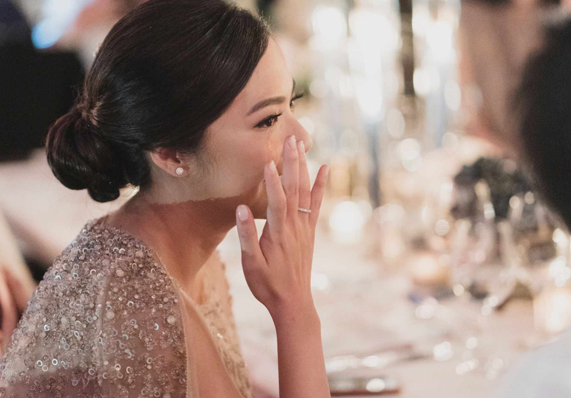 Bride wiping away a tear with naked nails