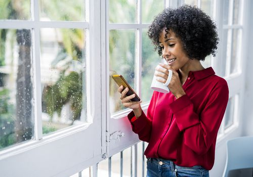 Smiling woman with cell phone standing next to window.