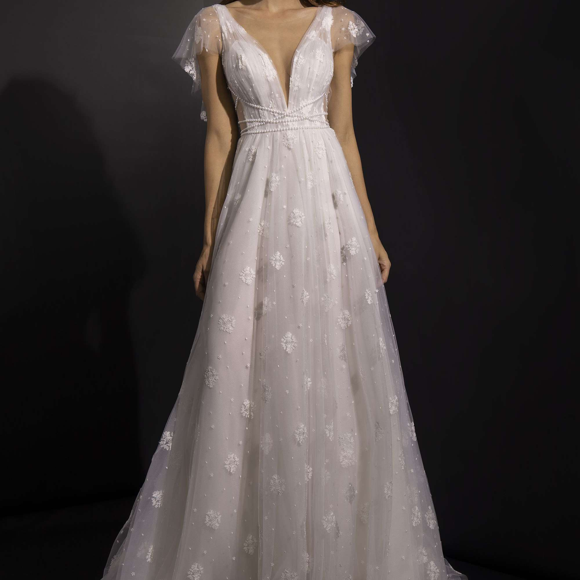 Model in V-neck A-line gown with tulle flutter sleeves and lace embellishments