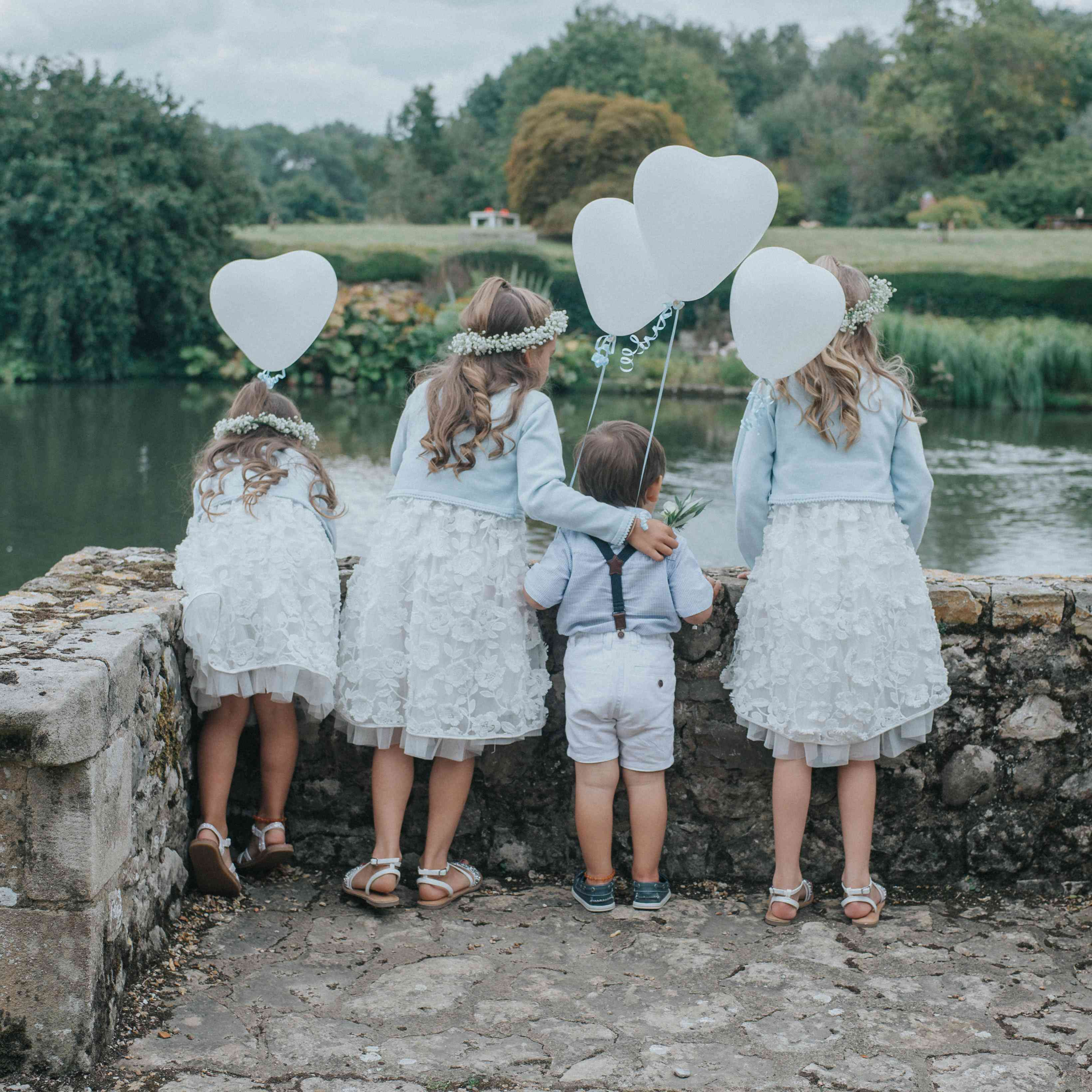 Three flower girls and one ring bearer looking out on body of water carrying white heart-shaped balloons