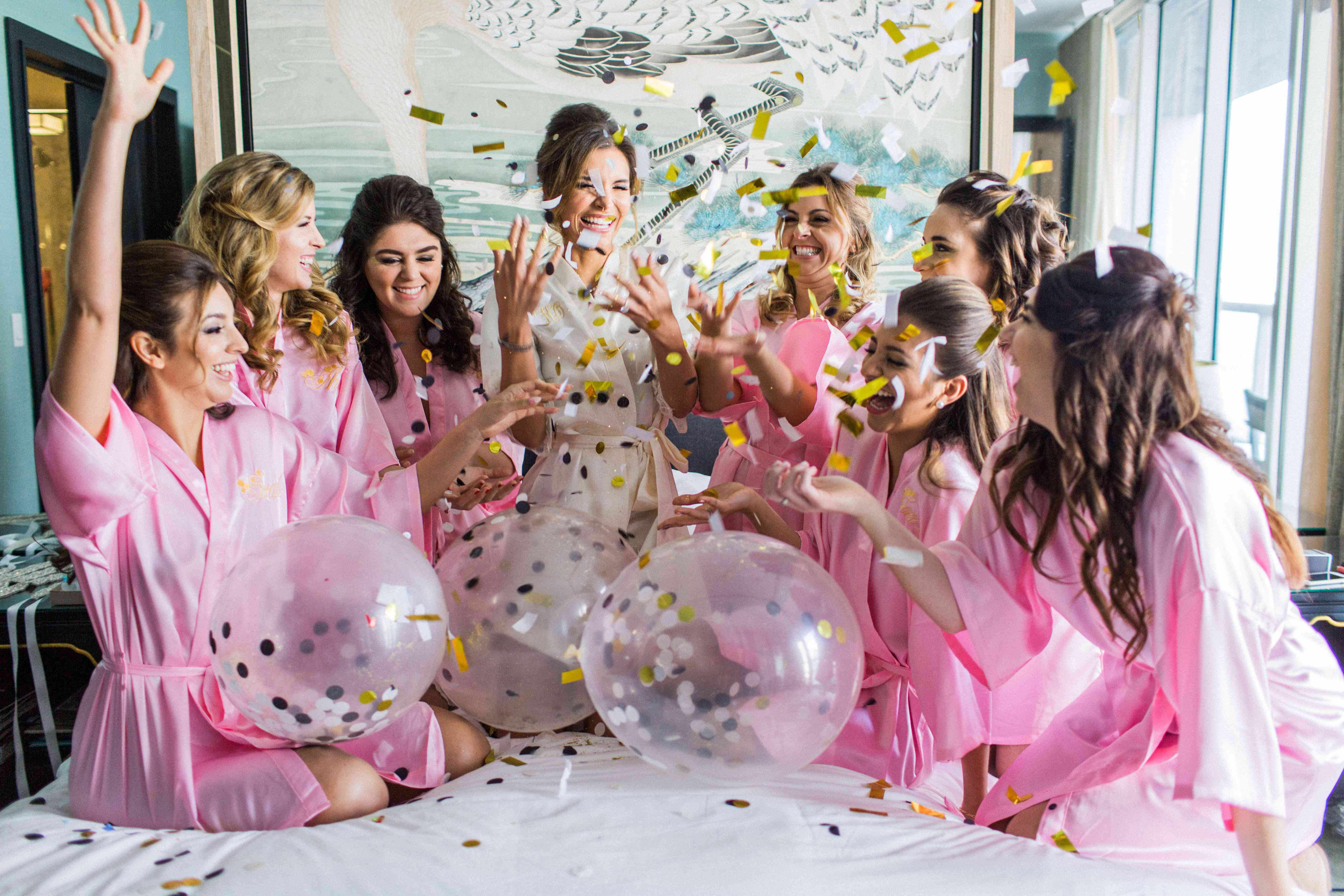 Bridesmaids in pink robes with confetti