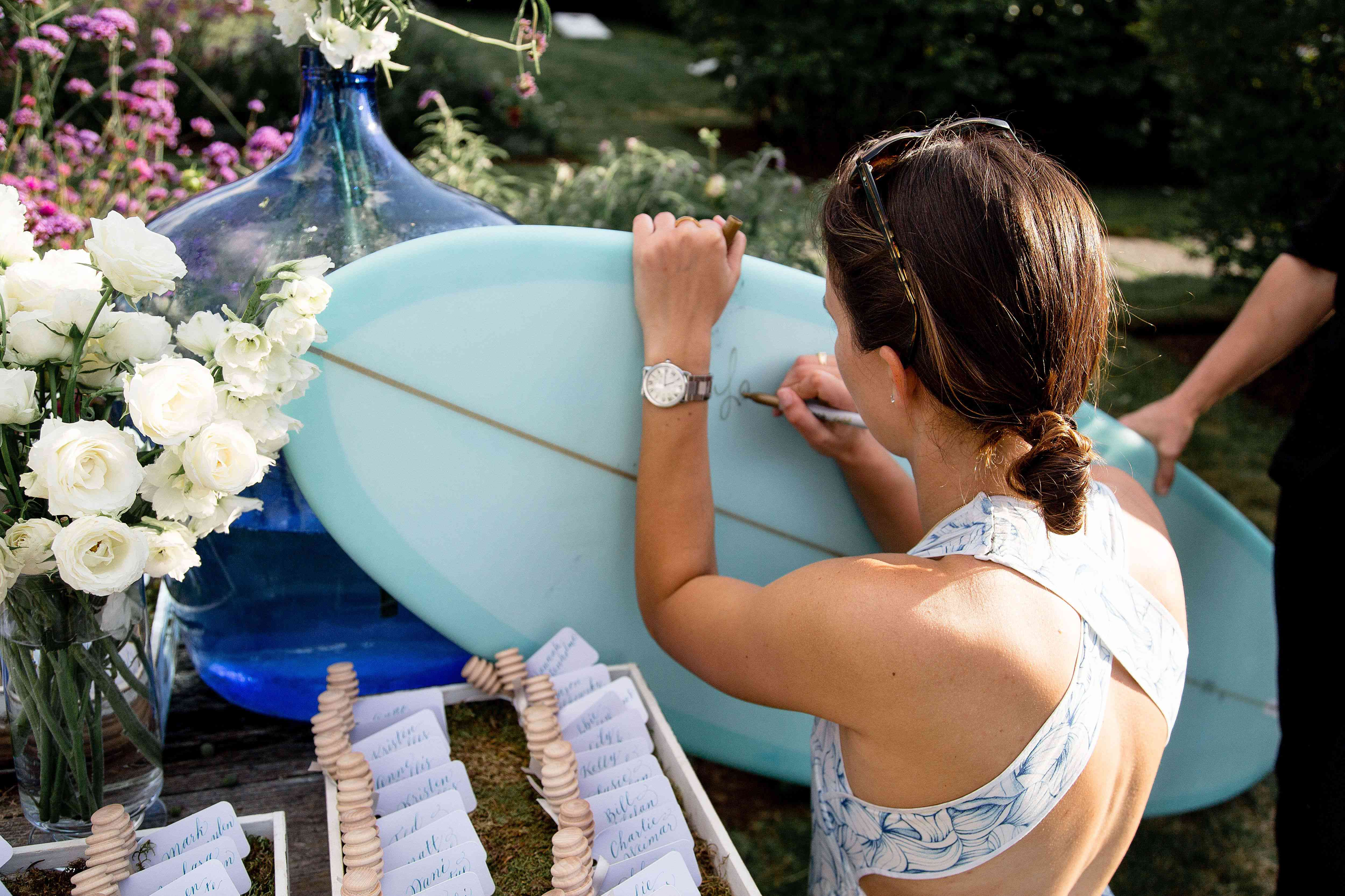 A guest signing a surfboard at a wedding