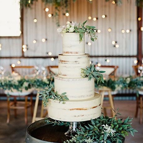 A thinly-frosted white wedding cake garnished with greenery by The Cake & I