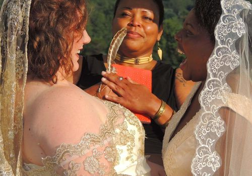 Wedding officiant looking at lesbian couple