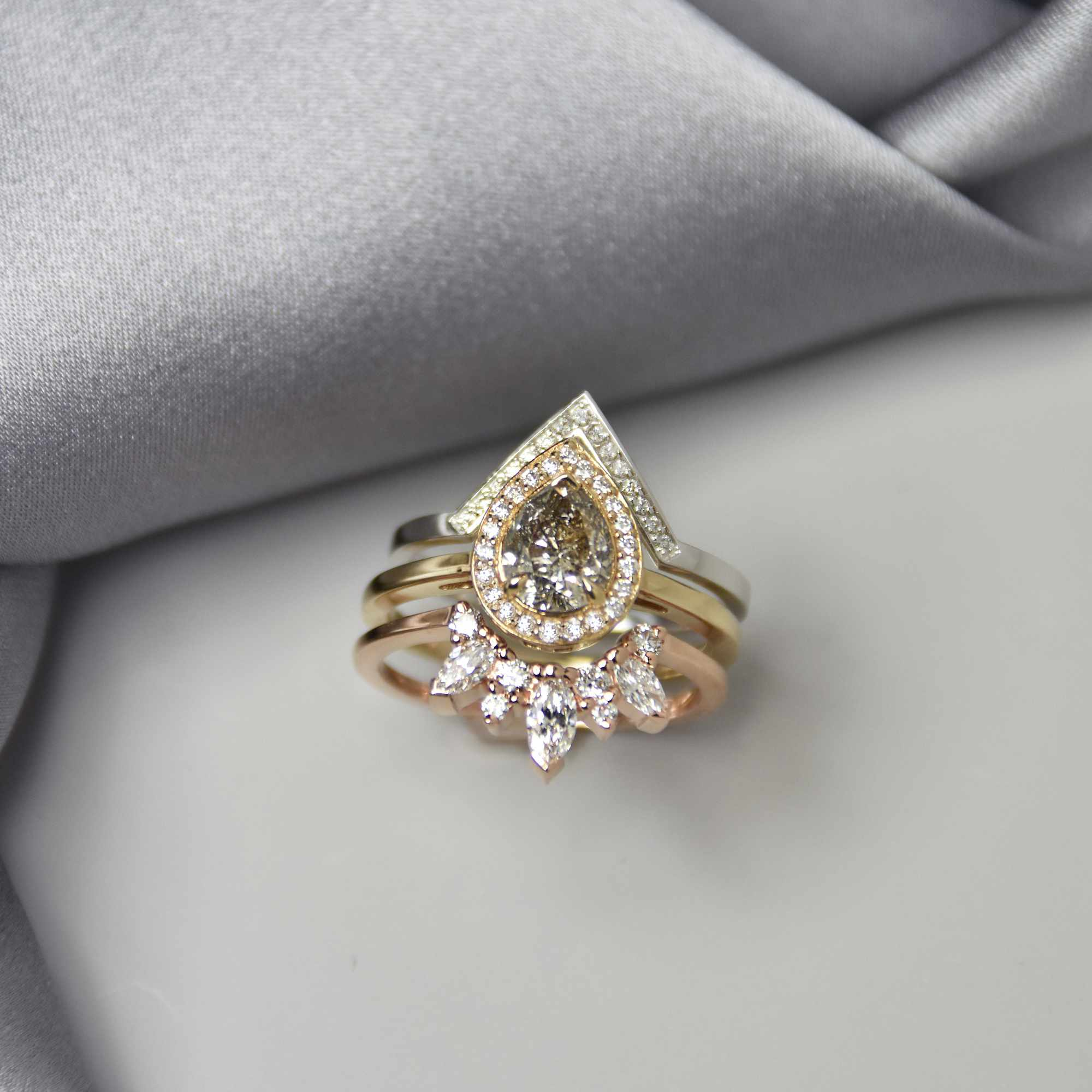 Stack of three rings with a pear shape diamond in the center