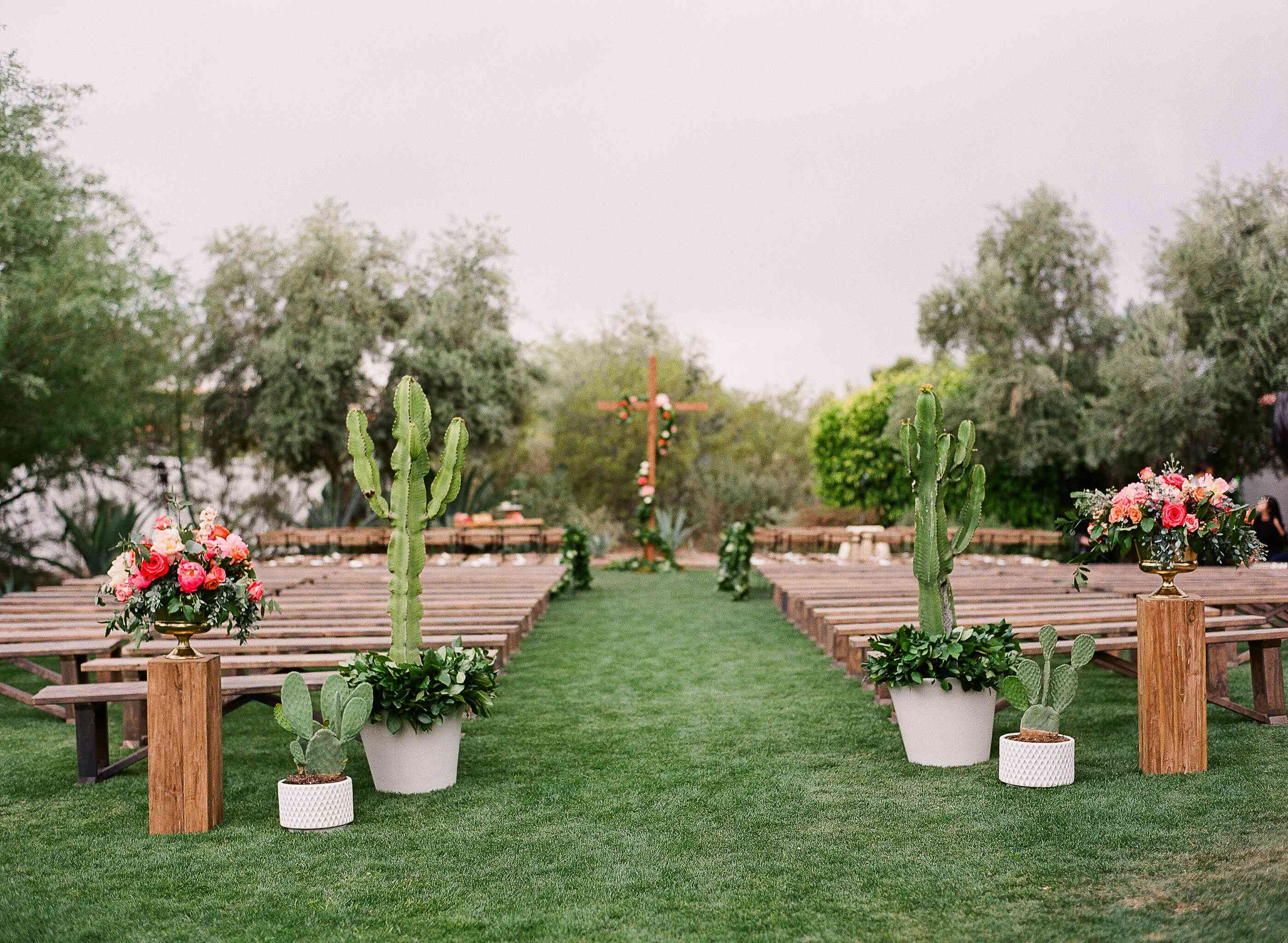 View looking down wedding aisle with tall cacti and pink flowers on either side of entrance